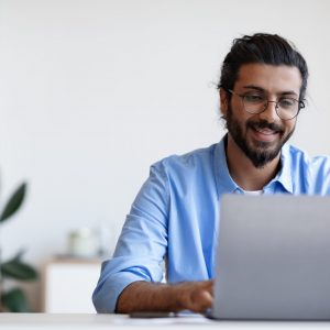 Recruitment Concept. Smiling Western Guy Using Laptop, Searching Job Online, Browsing Websites In Internet, Looking For Work Opportunities, Positive Indian Man Sitting At Desk At Home, Copy Space